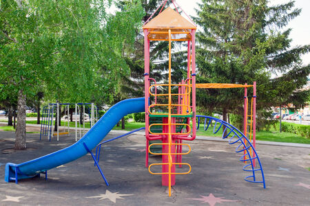 close-up colorful new playground with a slide and swings on a background of green trees in spring photo