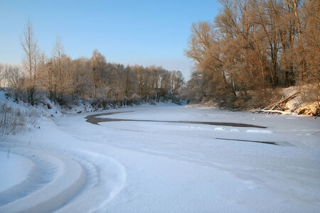 winter landscape of the river is covered with ice and snow, trees and grass on the shore covered with fluffy frost on a bright  frosty day photo