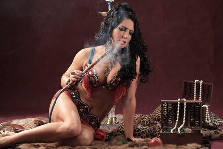 portrait of girl in beautiful clothes east smokes hookah lying on furs on burgundy background studio photo