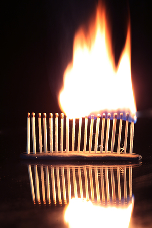 macro isolated burning matches set in a row on a mirror surface studio on a black background photo