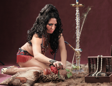 portrait of a girl sitting on a fur skin smokes hookah studio Stock Photo