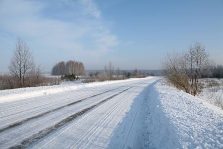 winter landscape of snowy road and woods on the horizon on a bright frosty day low angle view