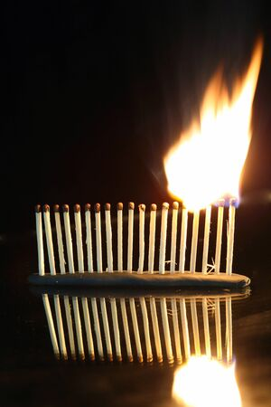 macro isolated burning matches set in a row on a mirror surface studio on a black background Stock Photo