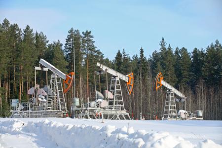 winter landscape oil pump near coniferous forest in sunny cold day