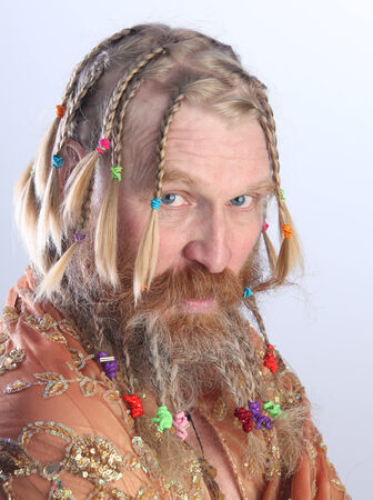 nude portrait of a man with a long beard, mustache and hair braided in pigtails with beige scarf studio on light background Stock Photo