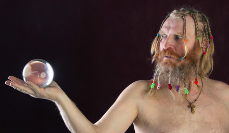 close-up portrait of a man with a long beard, mustache and hair braided in pigtails plays with glass sphere studio on dark background