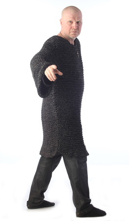 portrait of adult bald white man in chain mail on a light background studio Stock Photo
