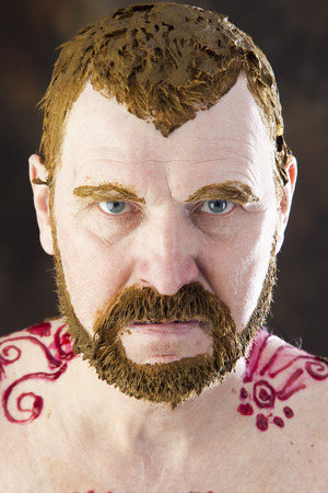 close-up portrait of an adult male with a naked torso and body painting with henna and colored hair and beard studio Stock Photo