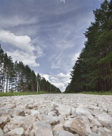 rocky road: rocky road near the pine forests and white clouds on blue sky in sunny summer day