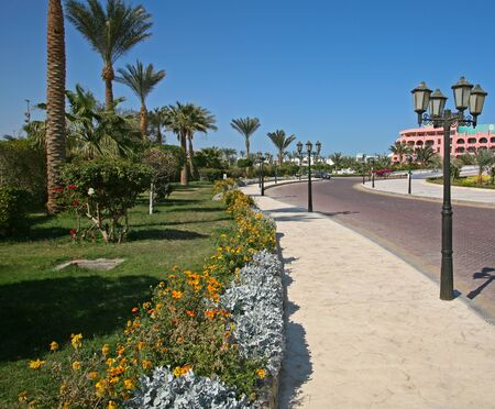 seaside resort hotel building and landscaped grounds with pool and flower beds on a hot sunny day photo