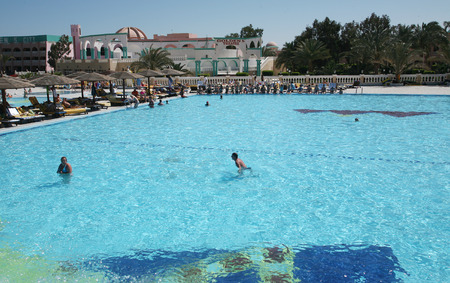 seaside resort hotel building and landscaped grounds with pool and flower beds on a hot sunny day