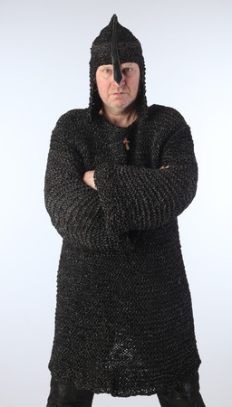 portrait of adult bald white man in chain mail and a helmet on a light background studio Stock Photo