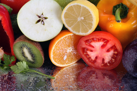 close-up of assorted cut ripe fruits and vegetables studio photo