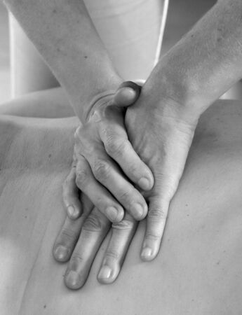 Isolated close-up of the hands of the masseur - female on mans back during a session, studio
