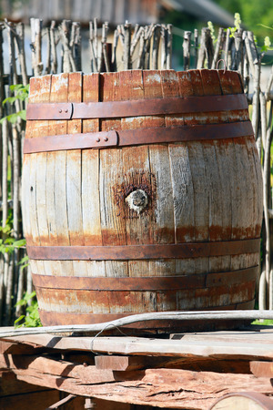 close-up of a big old wooden barrel with rusted metal rings in the village in summer