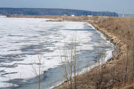 River landscape dissection and drift ice in the early spring, the trees on the shore with no leaves and cloudy sky photo
