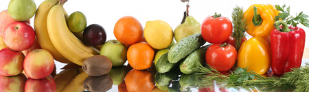 close-up of assorted ripe fruits and vegetables on a mirror surface on white background studio photo