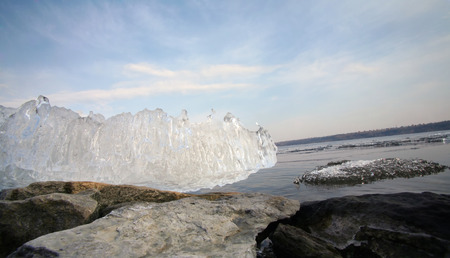 close-up of a piece of the melted ice on the river and the rocky shore photo