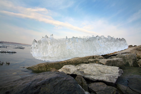 close-up of a piece of the melted ice on the background of the river and the rocky shore, view from below photo
