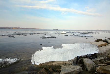 close-up of a piece of the melted ice on the  river and the rocky shore, view from below photo