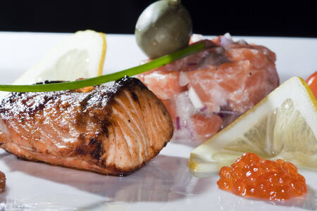 macro delicious dish of fried fish, caviar, lemon, decorated with cherry tomatoes and capers studio on dark  photo