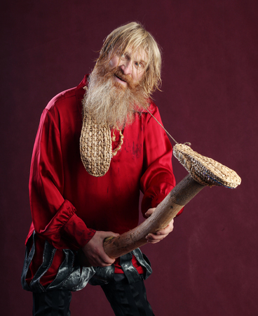 truncheon: portrait of a man in a red shirt with long hair beard and mustache with a baton and bast shoes in hands studio on a burgundy background