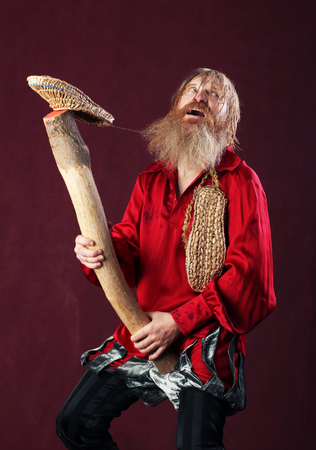 bast: portrait of a man in a red shirt with long hair beard and mustache with a baton and bast shoes in hands studio on a burgundy background