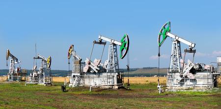 Sommerlandschaft Ölpumpen in den Getreidefeldern auf dem Hintergrund des blauen Himmels an einem sonnigen Tag Lizenzfreie Bilder