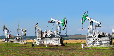 summer landscape oil pumps in the grain fields on the background of the blue sky on a sunny day Stock Photo