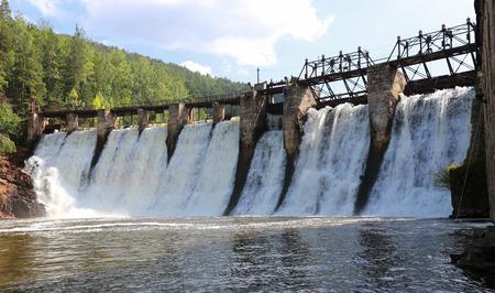 Sommerlandschaft des alten Staudamms am Fluss auf einem Hintergrund von Bergen und Wäldern an einem sonnigen Tag