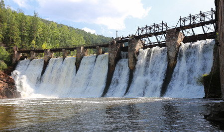 summer landscape of the old dam on the river on a background of mountains and woods on a sunny day Stock Photo