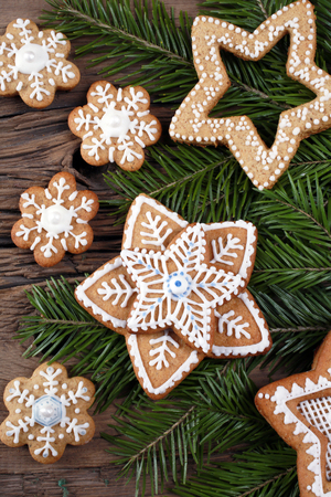 close-up still-life of fir branches and the gingerbread with pattern on magic Christmas holiday on background a wooden boards studio photo