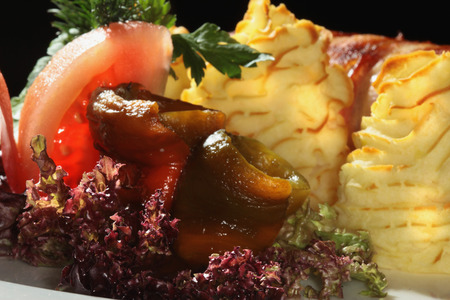 macro meatloaf with bacon and potato gratin decorated with greens and pickles photo