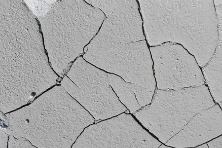isolated on gray: close-up texture isolated gray cracked earth in natural lighting Stock Photo