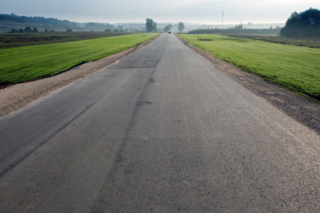 autumn landscape empty asphalt road among meadows leads to the horizon in the early misty morning photo