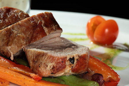 second meal: Close-up of meat with vegetables garnish on a white plate on a black studio