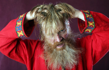 close-up portrait of the blessed with a long beard and a mustache and wet blond hair in a red shirt studio Imagens