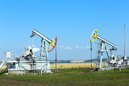 grain fields: summer landscape oil pumps in the grain fields on the background of the blue sky on a sunny day Stock Photo