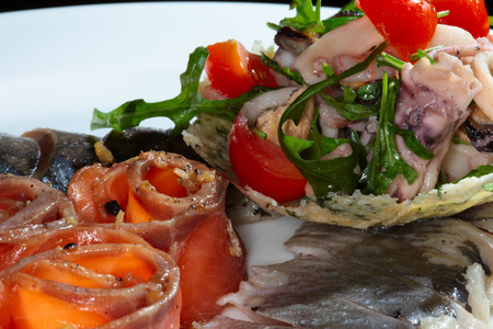 seafish: close-up sliced fish of different varieties decorated with greens and tomatoes on white dish