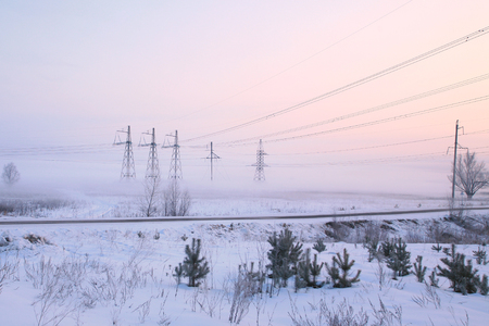 forest railway: winter landscape railway tracks and power lines in the snow-covered field near the forest foggy morning