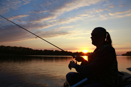 Fishing pole: Portrait of a man in profile in a boat on a river with a fishing pole in his hands at sunset in autumn