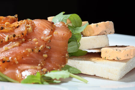 Close-up of fried toast with smoked red fish and greens on white plate studio Stock Photo
