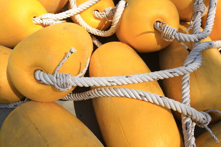 associated: isolated close-up of yellow floats associated with white rope