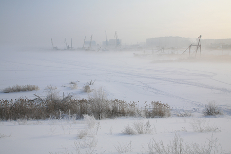 winter landscape river port misty morning, cranes and ships laid up in the ice photo