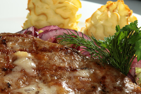 second meal: macro steak with potato gratin decorated with greens and onion Stock Photo