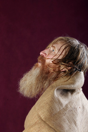 close-up portrait in profile of the blessed with a long beard and a mustache and wet blond hair wrapped in burlap studio