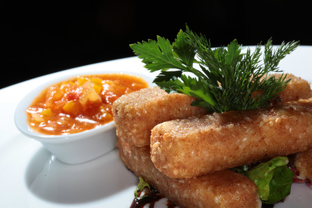 close-up of fish fingers with vegetables and sauce on a white plate photo