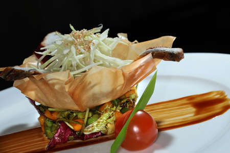 second meal: close-up gourmet salad with fish and vegetables in a basket made of dough on black studio Stock Photo