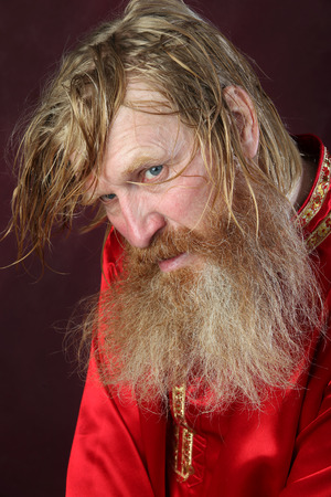 close-up portrait of the blessed with a long beard and a mustache and wet blond hair in a red shirt studio Stock Photo