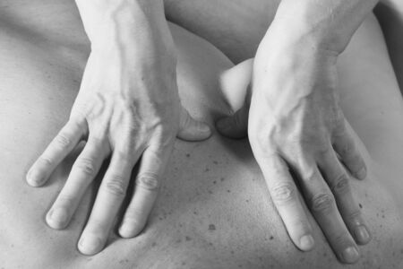 body massage: Isolated close-up of the hands of the masseur - female on mans back during a session, studio